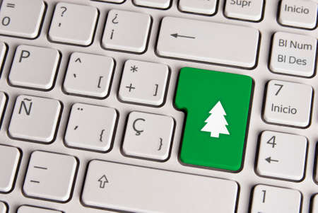 Spanish keyboard with Merry Christmas tree icon over green background button. photo