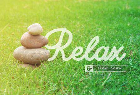 armonia: Relájese y frenar cita inspiradora motivación zen con piedras de equilibrio y fondo de la hierba verde ideal para spa y cartel de bienestar.