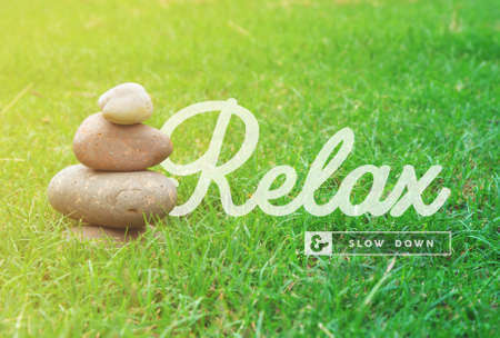 wellness: Relax and slow down motivational inspiring quote with balance zen stones and green grass background ideal for spa and wellness poster. Stock Photo