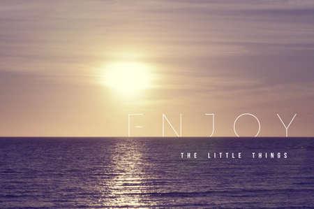 Genießen Sie die kleinen Dinge, motivierend inspirierend Zitat-Konzept mit weichem Licht Sommer Sonnenuntergang Landschaft Hintergrund ideal für Druckkarte und Plakatgestaltung. Standard-Bild