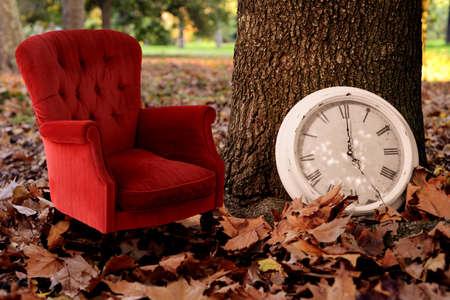 silla de madera: Relájese se Caída concepto de tiempo de fondo de la vendimia. Dile a un historial de otoño idea de la fotografía creativa con el árbol, el reloj y sofá rojo en las hojas temporada de fondo del parque.