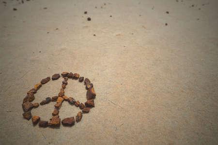 simbolo della pace: Simbolo di pace fatto con rocce sulla spiaggia di sabbia. pantaloni a vita bassa Estate sfondo. Archivio Fotografico