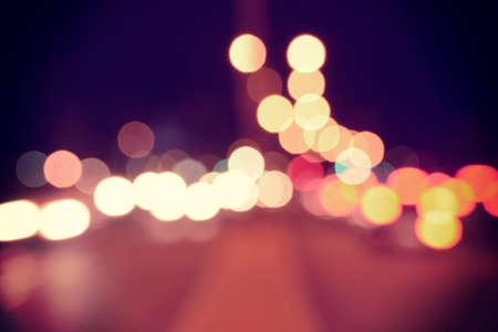 Blur urban car lights bokeh background with vintage filter effect.