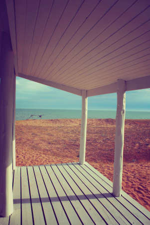 quiet: White beach house porch with vintage style filter effect and ocean view background.