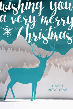 hand card: Merry christmas Happy New Year 2016 handmade paper cut art winter scene: blue deer papercraft with snow forest landscape and text label. Ideal for holiday greeting card, xmas poster or campaign.