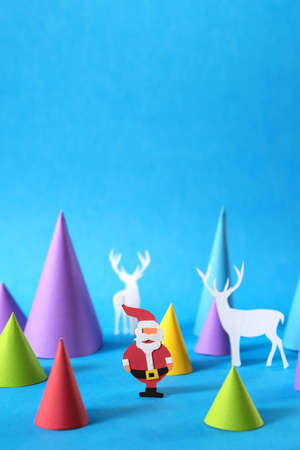 craft paper: Christmas colorful paper craft scene with santa, deer silhouettes and xmas pine tree shapes, includes copy space. Ideal for holiday greeting card, poster or web. Stock Photo
