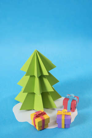 cut paper: Christmas tree in paper cut handmade style with gift boxes on colorful blue background. Ideal for xmas greeting card, holiday poster or web.
