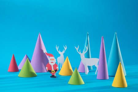 conceito: Natal 3d de papel artesanal cortar Santa com veados e formas coloridas pinheiro. Ideal para o cartão do cumprimento do xmas, poster férias ou web. Banco de Imagens