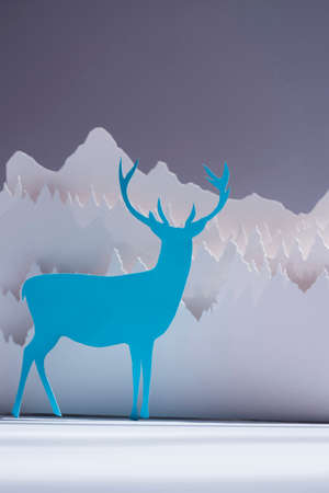 craft paper: Handmade paper cut deer in blue color with snow forest background. Ideal for holiday greeting card, christmas, new year or campaign.