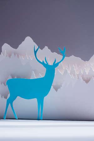 paper craft: Hecho a mano ciervos corte de papel en color azul con el fondo del bosque de la nieve. Ideal para tarjetas de felicitación de vacaciones, navidad, año nuevo o campaña.