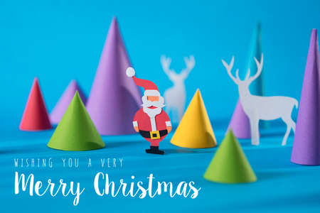 hand craft: Merry Christmas handmade paper cut santa and deer with colorful 3d cone pine tree shapes.Illustration background ideal for xmas greeting card, poster or campaign.
