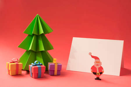 craft paper: Merry Christmas paper cut scene: Xmas pine tree with gifts and empty greeting card template. Includes clipping path to display your own design. Stock Photo