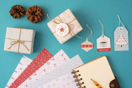 handmade: Merry Christmas season concept stationery mockup top view set template: empty paper notebook with pencil, vintage gift boxes, labels and stationery elements. Stock Photo