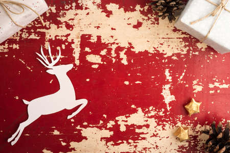 wooden box: Vintage christmas time top view concept scene with copy space. Retro holiday decoration and paper cut reindeer silhouette on red grunge wood background. Stock Photo