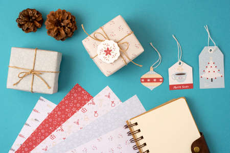 label tag: Merry Christmas top view composition with stationery set template. Spiral notebook with copy space and wrapping paper stack, vintage gift boxes and holiday decoration.