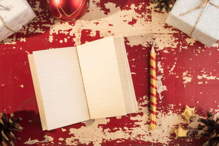 notebook paper background: Holiday concept, top view empty paper notebook with pencil and vintage hipster Christmas ornament decoration on grunge wood texture background.