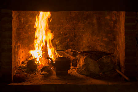 burning time: Traditional fireplace stove with fire burning and kettle. Winter time comfort concept.
