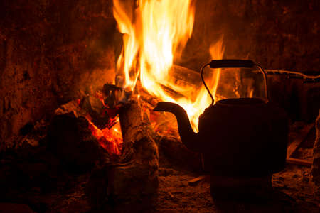 bonfires: Kettle in fireplace, fire and wood burning. Cozy winter holiday cabin scene. Stock Photo