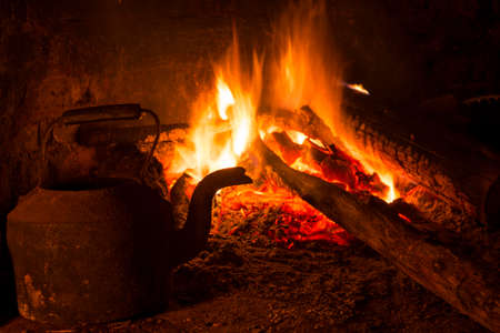 logs: Old brick fireplace with burning wood and kettle. Winter time warm indoors scene.