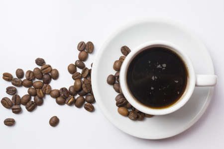Top view, traditional cup of black coffee with beans over white background. Reklamní fotografie