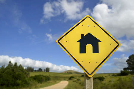rural road: Buy your own house in the countryside, way to the home of your dreams concept. Road sign with real estate icon in nature rural environment, includes copy space.