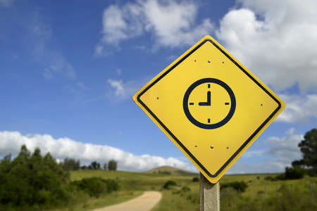 rural road: Time to travel and get in touch with nature concept. Clock icon road sign in rural scene, includes copy space.