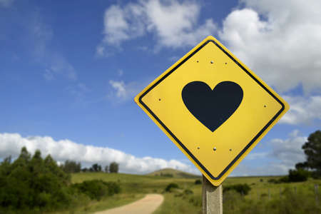 rural road: Natural way to find the love of your life concept. Road sign with heart shape icon in rural scene, includes copy space.