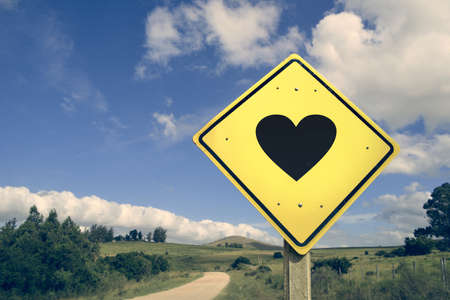 Love heart shape romantic concept icon road sign on empty countryside nature landscape, vintage filter effect.