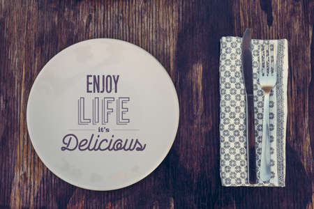 enjoy life: Vintage rustic top view concept. Plate and cutlery on old wood background with enjoy life, it is delicious text quote.