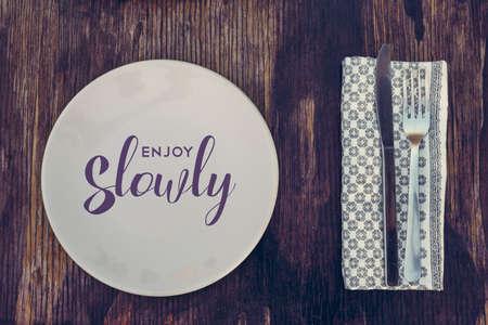 slowly: Disfrutar lentamente cita, diseño concepto de alimentación saludable con elementos retro restaurante sobre la superficie de madera de estilo.
