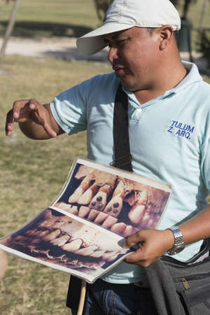 roo: TULUM, QUINTANA ROO, MEXICO – FEBRUARY 22, 2016: Local tourist guide teaches tourist group about mayan civilization in Tulum archaeological site. Editorial