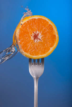 vibrant colors: Fresh orange fruit on fork with vibrant colors and cool water splash. Ideal for organic food campaign, health poster or web.
