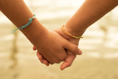 Close up of two children holding hands on the beach sand, summertime friendship concept.