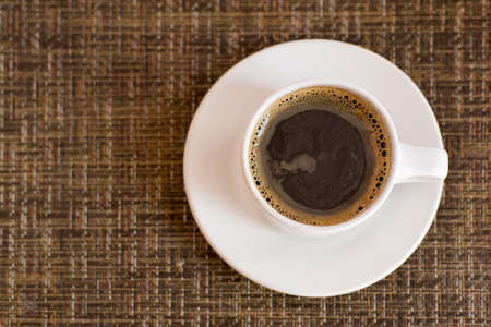 wicker work: Top view of dark coffee in white mug and plate on wicker texture table background.