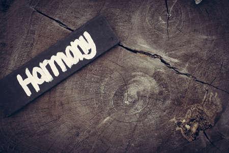 armonia: concepto de la armonía, la mano vintage Muestra pintada sobre la textura de fondo de madera rústica.