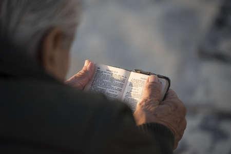 Un más viejo hombre que lee la biblia santa en español visto desde el ángulo de visión del hombro, el concepto de religión.