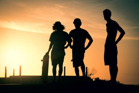 skate board: Silhouettes of friend group standing at skate board ramp, summer sunset background. Stock Photo