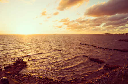 shore: Panoramic view of ocean beach shore with rocks and sunset view landscape. Stock Photo