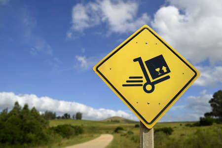 cart road: Fast shipping service everywhere; package box concept. Road sign with delivery cart icon in rural landscape; includes copy space.
