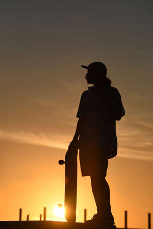 skate park: Silhouette of teen boy at skate park on a golden summer sunset sky, includes clipping path.