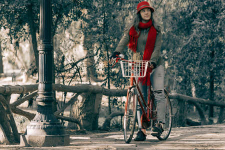 Girl riding bike at park wearing red urban fashion on beautiful autumn day, vintage contrast effect.