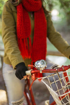 handlebars: Close up of vintage bike bell, basket and handlebars with girl in urban fashion riding bicycle outdoors.