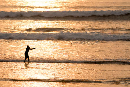 fish net: Fisherman throwing fish net on beach coast, summer calm scene at sunset time with golden sunlight on waves. Stock Photo