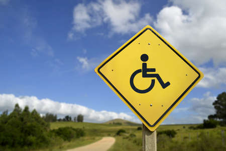 wheelchair access: Easy access for all people and inclusive support concept. Road sign with wheelchair disability icon on rural environment, includes copy space.