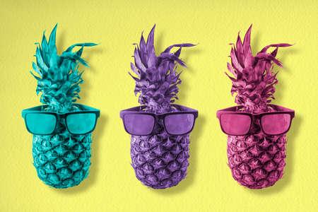Drie trendy ananasvruchten die koele hipsterzonnebril in kleurrijke retro stijl, gelukkig van het de achtergrond zomerconcept art. Dragen. Stockfoto