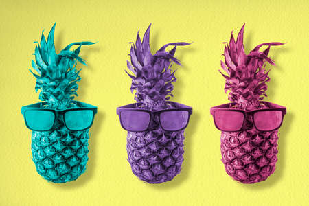 Three trendy pineapple fruits wearing cool hipster sunglasses in colorful retro style, happy summer concept background art.