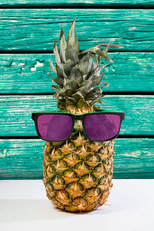 Trendy summer pineapple wearing hipster style sunglasses with beach wood texture color background.