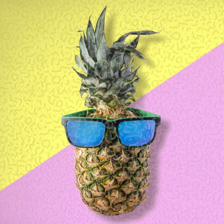idea: Happy summer concept idea, fun pineapple fruit wearing hipster style sunglasses on colorful background.