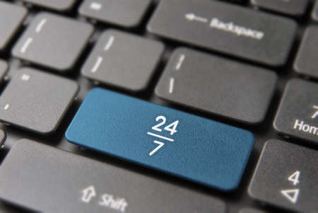 Online business always open concept: blue key button with 24/7 working hours symbol on laptop keyboard.