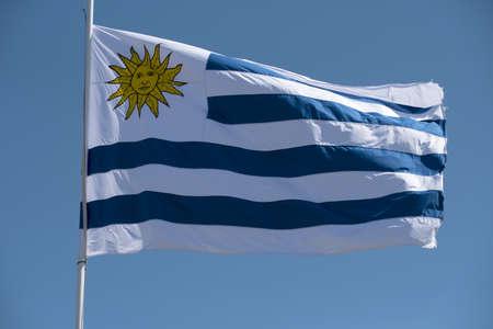 Drapeau uruguayen dans le vent sur fond de ciel bleu. Mât de drapeau du pays de l'Uruguay avec emblème national.